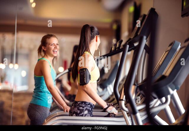 Zwei passen Frauen laufen auf Laufbändern im modernen Fitnessraum Stockbild