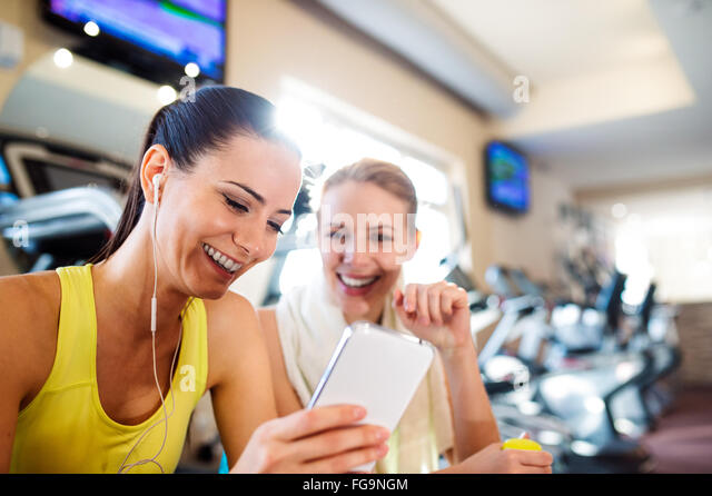 Passen zwei attraktive Frauen im Fitness-Studio mit Smartphone Stockbild