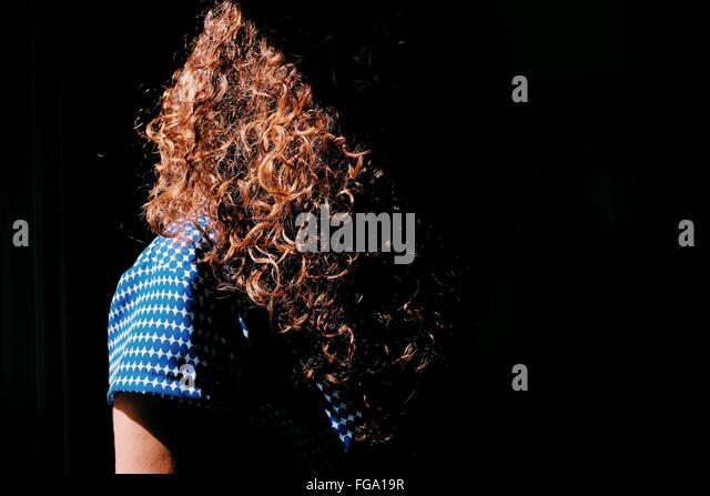 Frau mit lockigen braunen Haaren im Sonnenlicht Stockbild