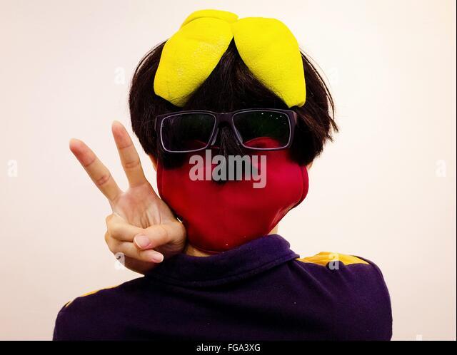 Rückansicht der Person mit Brille und Maske mit Peace-Zeichen auf weißen Hintergrund Stockbild
