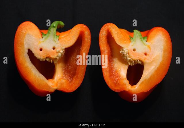 Auf schwarzem Hintergrund Orange Paprika schneiden Stockbild