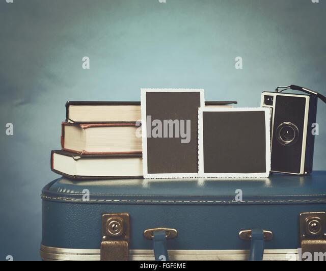 Alte Fotografien, eine Kamera und Bücher stehen ganz oben auf einem Vintage Koffer mit einem blauen Hintergrund Stockbild