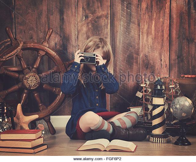 Ein kleines Kind hält eine alte Retro-Kamera mit Reisen Objekte im Hintergrund für einen Urlaub Kunst Stockbild