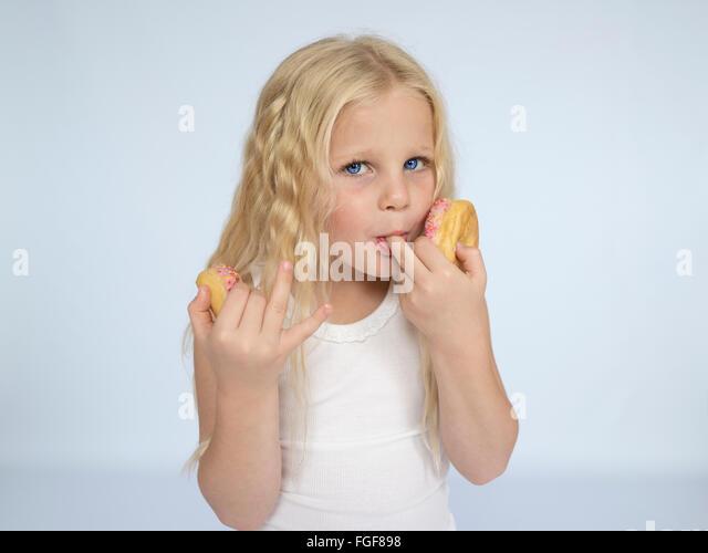 Junges Mädchen mit langen blonden Haaren Essen Donuts und leckte ihre Finger Stockbild