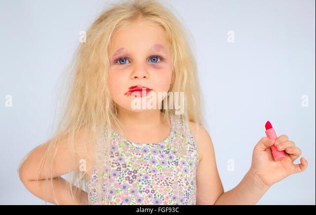 Junges Mädchen mit blonden Haaren tragen verschmierte Make-up hält einen roten Lippenstift Stockbild