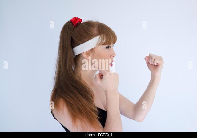 Frau mit langen braunen Haaren tragen Kopf Schweißband mit ihrer geballten Fäusten Boxen betreiben wird Stockbild