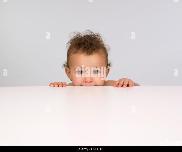 Niedliche Baby Boy über eine Tischplatte gucken Stockbild