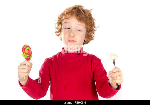 Junge mit Süßigkeiten und Obst entscheiden zwischen gesunden und ungesunden Stockbild