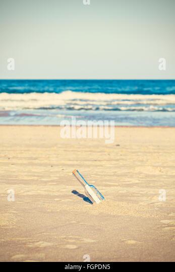 Gecrosst wird Foto einer Flasche mit Buchstaben am Strand, geringe Schärfentiefe. Stockbild