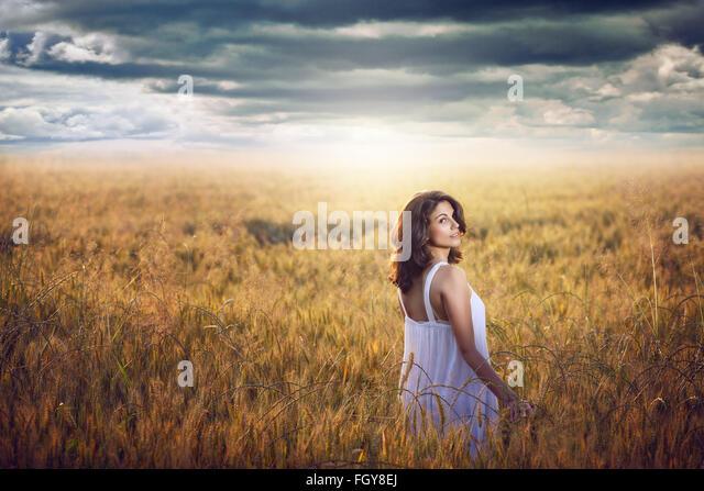 Schöne Frau in einem Kornfeld mit dramatischen Himmel. Abendlicht Stockbild