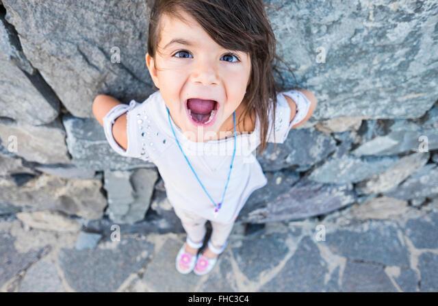 Porträt von kleinen Mädchen mit Mund zu öffnen, vor einer Felswand Stockbild