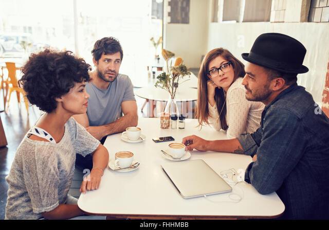 Porträt der jungen Männer und Frauen sitzen in einem Café-Tisch und reden. Gruppe junger Freunde Stockbild