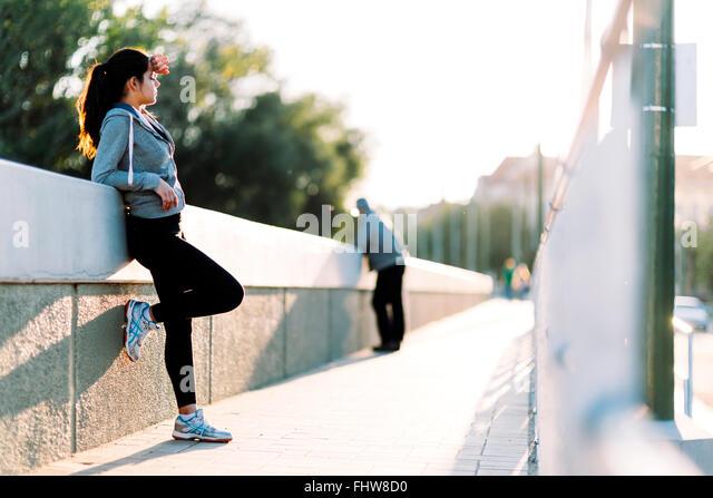 Schöne Frau ruht in der Stadt nach dem Joggen am Morgen Stockbild