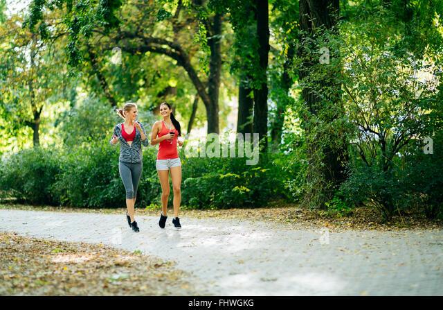 Sportliche Frauen im Park Joggen und Musik über Kopfhörer hören Stockbild