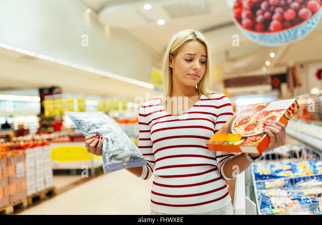 Schöne Frau entscheiden, was zu kaufen, anhand was gesünder ist Stockbild