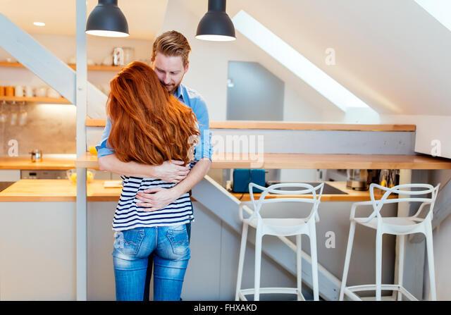 Schönes Paar glücklich für ihr neues Zuhause und umarmt nach dem Umzug in Stockbild