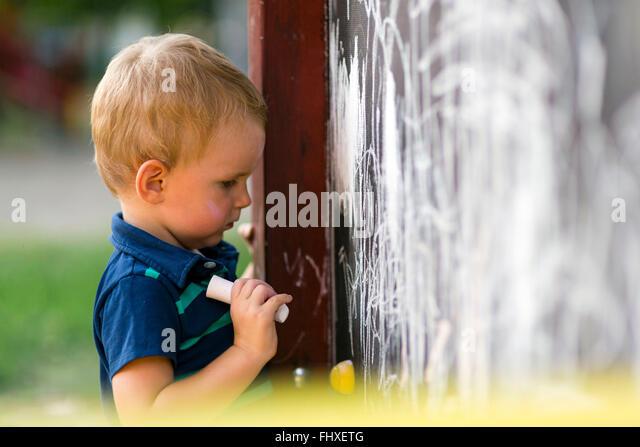 Kreative niedlichen Kleinkind zeichnen mit Kreide im Freien auf dem Reißbrett Stockbild