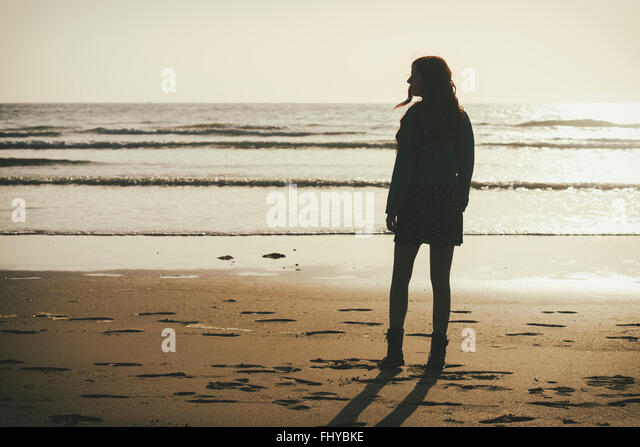 Spanien, Cadiz, junge Frau am Meer von twilight Stockbild