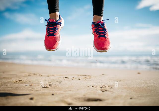Springen Sie ein paar Füße beschuht in Turnschuhen, am Strand Stockbild