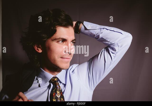 Mann warf eine Hand hinter seinem Kopf und auf der Suche. Stockbild