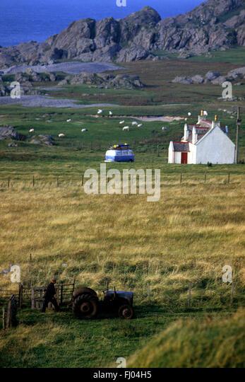 ein Alter Traktor und Bauer steht auf der einen Seite des Feldes zu einer Hütte und VW-Bus mit Surfbrettern Stockbild