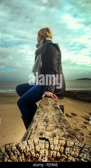 junge Frau sitzt auf Holz am Strand Stockbild