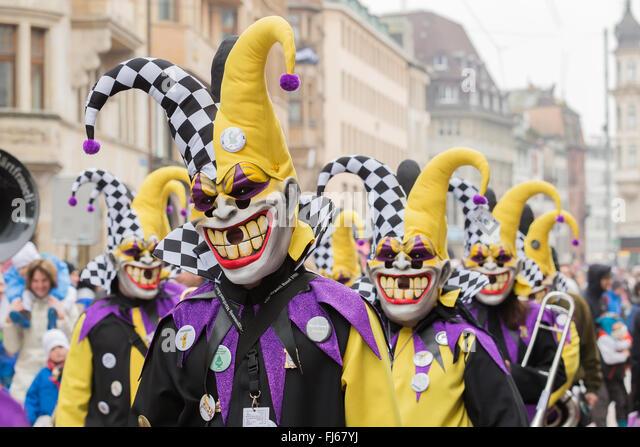 Die Parade der Basler Fasnacht in der Schweiz, mit Clowns, bunten Kostümen, das Konfetti auf die Zuschauer Stockbild