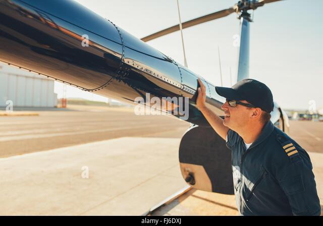 Männliche Pilot prüft das Heck des Hubschraubers vor dem Flug. Mechanische Kontrolle Hubschrauber vor Stockbild