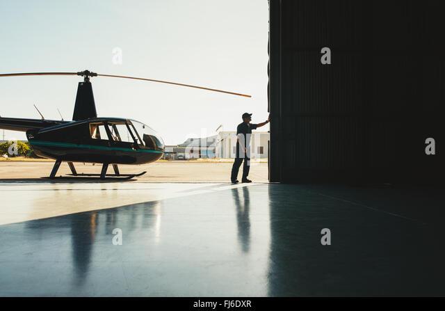 Mechaniker, die Öffnung der Tür von einem Flugzeughangar mit einem Helikopter Stockbild