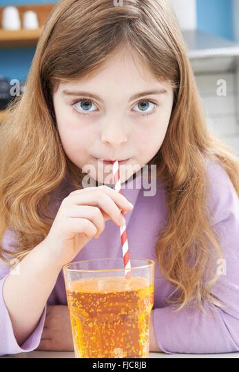 Junges Mädchen Glas Soda mit Strohhalm trinken Stockbild
