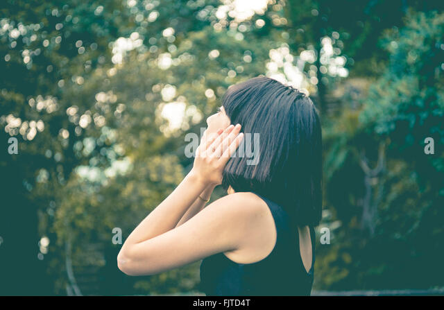 Nahaufnahme von Frau wegschauen gegen Bäume Stockbild