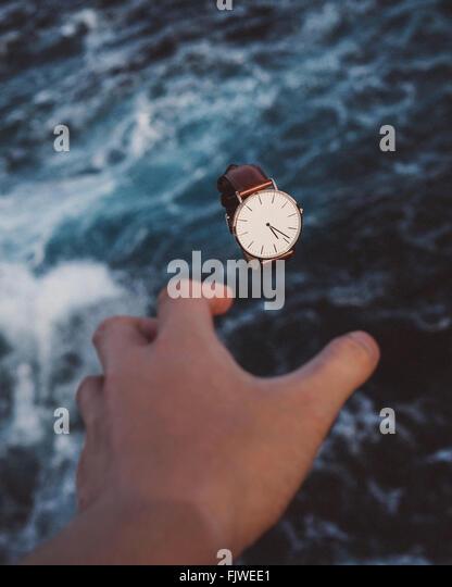 Hand greift Armbanduhr über Meer abgeschnitten Stockbild