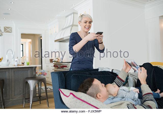 Mutter fotografiert Mann und Baby Sohn auf sofa Stockbild