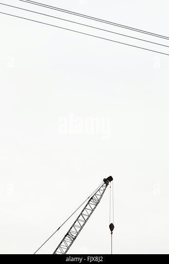 Niedrigen Winkel Ansicht von Kran und Elektrokabel gegen klaren Himmel Stockbild