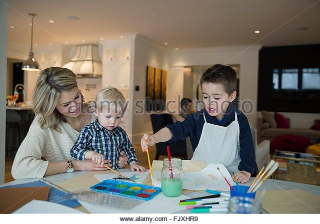 Mutter und Söhne Aquarellmalerei am Tisch Stockbild