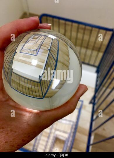Zugeschnittenes Bild der Person, die Kristallkugel mit Reflexion der Wendeltreppe Stockbild
