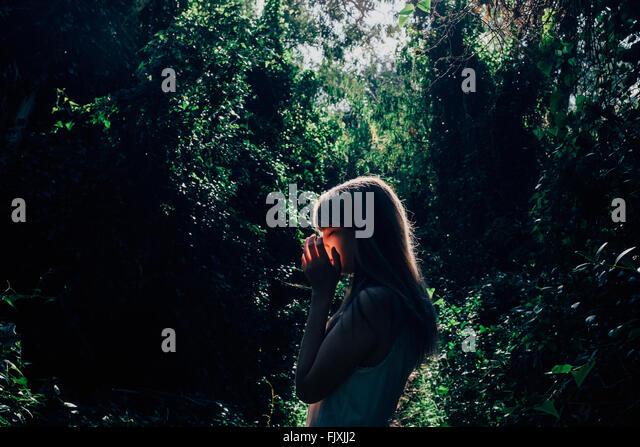 Seitenansicht der jungen Frau gegen Bäume im Wald Stockbild