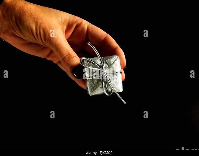 Close-up Of Hands Holding Geschenk auf schwarzem Hintergrund Stockbild