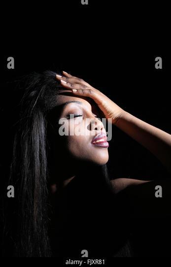 Nahaufnahme des Mode-Modell mit der Hand auf der Stirn vor schwarzem Hintergrund Stockbild