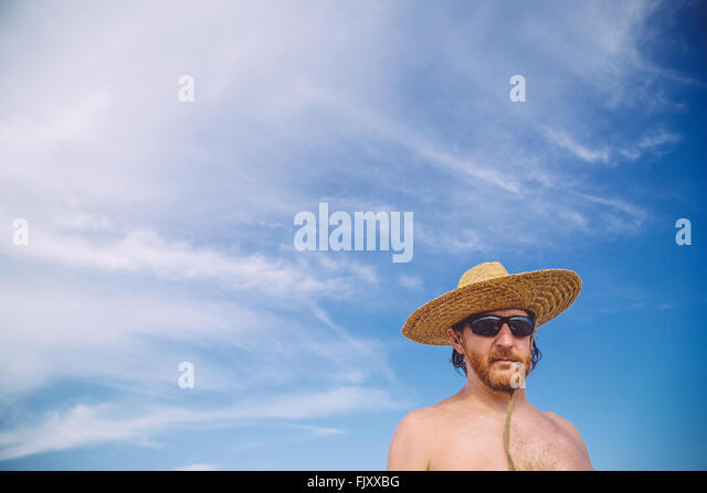 Niedrigen Winkel Blick auf nacktem Oberkörper reifer Mann mit Hut gegen Himmel Stockbild