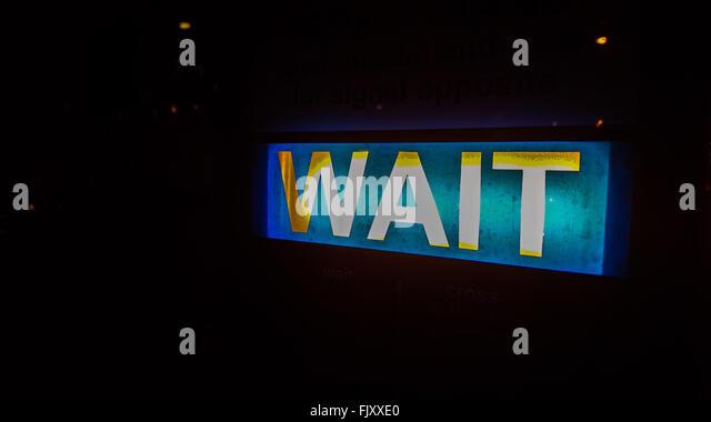 Nahaufnahme des beleuchteten warten Zeichen Stockbild