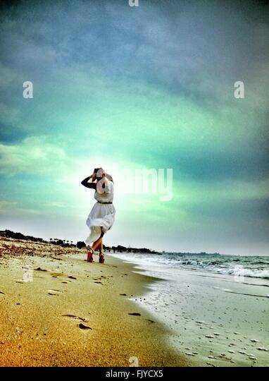 Niedrigen Winkel Blick der jungen Frau zu Fuß am Strand gegen bewölktem Himmel Stockbild