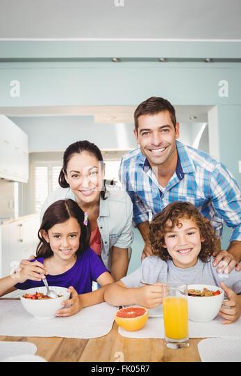 Fröhlicher Mensch und Frau mit den Kindern frühstücken Stockbild