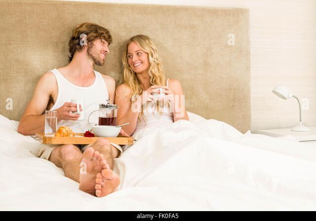 Nettes Paar mit Frühstück im Bett Stockbild