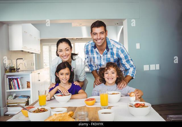 Glücklicher Mann und Frau mit den Kindern frühstücken Stockbild