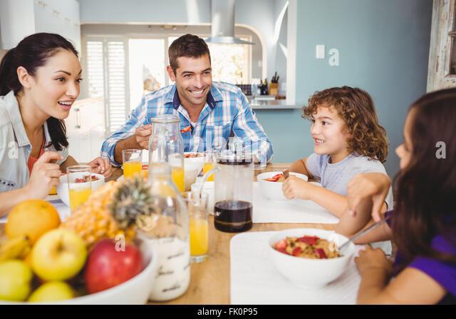 Fröhliche Familie frühstücken am Tisch Stockbild