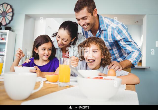 Fröhlicher Mensch und Frau mit den Kindern während des Frühstücks Stockbild