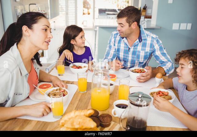 Glückliche Familie im Gespräch beim Frühstück Stockbild