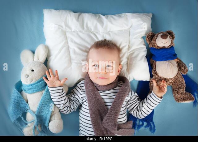 Krank im Bett liegen junge Stockbild