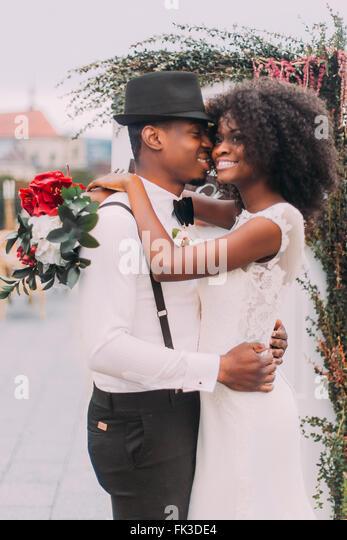 Glückliche afrikanische Hochzeitspaar umarmt auf dem Dach Stockbild